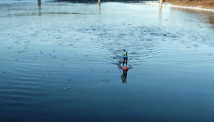 Stand-up paddleboarder hits the river all winter long